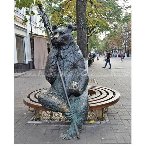 Metal Bear Statue Sitting on Bench with Apple Garden